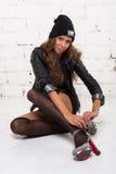 一件黑夹克和一个帽子的时兴的女孩有微笑礼鞋的 白色砖墙,没被隔绝 库存照片