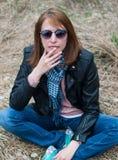 一件黑夹克和牛仔裤的少妇坐干草 库存图片