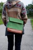 一件夹克的女孩有从后面的一个袋子的 免版税库存图片