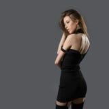 一件黑套衫连超短裙的俏丽的妇女 免版税库存图片