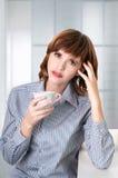 一份女实业家饮用的咖啡在办公室 免版税库存图片