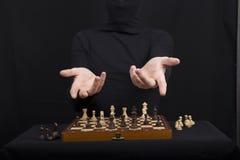 一件黑女衬衫的女孩握在一个木棋盘的手与 免版税库存图片