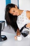 一份妇女倾吐的咖啡的照片从一个玻璃罐的 图库摄影