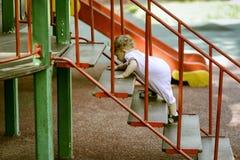 一年孩子爬上在操场的台阶 免版税库存图片
