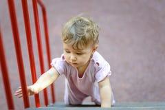 一年孩子爬上在操场的台阶 免版税图库摄影