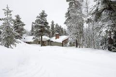 一间客舱在雪盖的森林里 库存图片