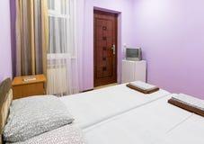 一间小屋子的内部有一个双人床、窗口、电视和冰箱的 图库摄影