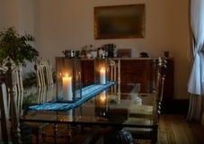 一间屋子的美好的内部有站立两个蜡烛烧灯的玻璃桌的 免版税库存照片