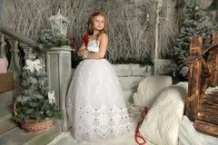 一件巧妙的白色礼服的美丽的白肤金发的女孩孩子在圣诞节装饰 免版税库存照片
