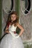 一件巧妙的白色礼服的美丽的白肤金发的女孩孩子在圣诞节装饰 库存图片