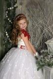 一件巧妙的白色礼服的美丽的白肤金发的女孩孩子在圣诞节装饰 库存照片