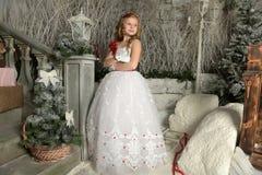 一件巧妙的白色礼服的美丽的白肤金发的女孩孩子在圣诞节装饰 图库摄影