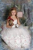 一件巧妙的白色礼服的美丽的白肤金发的女孩孩子有玩具的 图库摄影