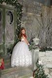 一件巧妙的白色礼服的美丽的白肤金发的女孩孩子 免版税图库摄影