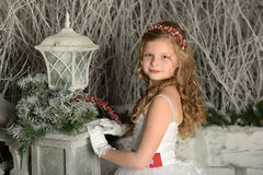 一件巧妙的白色礼服的美丽的白肤金发的女孩孩子 图库摄影