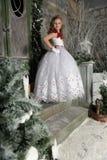 一件巧妙的白色礼服的美丽的白肤金发的女孩孩子 免版税库存图片