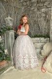 一件巧妙的白色礼服的美丽的白肤金发的女孩孩子 库存照片