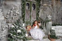 一件巧妙的白色礼服的美丽的白肤金发的女孩孩子 库存图片