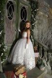一件巧妙的白色礼服的美丽的白肤金发的女孩孩子 免版税库存照片