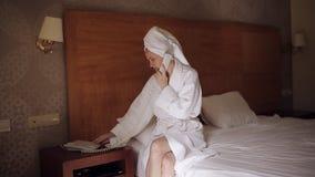一件浴巾的一名妇女在阵雨以后喝咖啡和电话到总台 股票录像