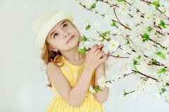一件帽子和黄色礼服的迷人的小女孩金发碧眼的女人在光 免版税库存图片