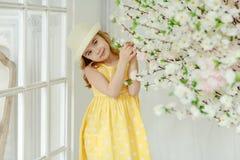 一件帽子和黄色礼服的迷人的小女孩金发碧眼的女人在光 免版税库存照片
