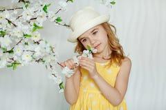 一件帽子和黄色礼服的迷人的小女孩金发碧眼的女人在光 免版税图库摄影