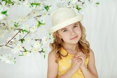 一件帽子和黄色礼服的迷人的小女孩金发碧眼的女人在光 库存图片