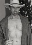 一件开放长袍的一位牛仔由圣诞树 库存图片