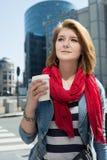 一份年轻微笑的妇女饮用的咖啡的画象从纸m的 库存图片