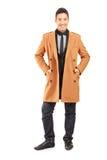 一件微笑的英俊的人佩带的外套的全长画象 免版税图库摄影