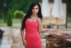 一件性感的桃红色礼服的美丽的女孩 免版税库存图片