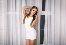 一件性感的白色礼服的美丽的女孩 图库摄影