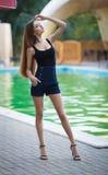 一件性感的礼服的美丽的女孩在水池附近 库存照片