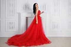 一件性感的红色礼服的美丽的女孩 免版税库存照片