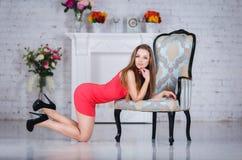 一件性感的红色礼服的美丽的女孩 免版税库存图片