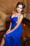 一件性感的蓝色礼服的美丽的女孩 图库摄影