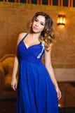 一件性感的蓝色礼服的美丽的女孩 库存图片