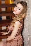 一件性感的金礼服的美丽的女孩 免版税库存照片