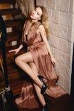 一件性感的金礼服的美丽的女孩 库存照片