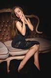 一件性感的黑礼服的美丽的女孩 免版税库存图片