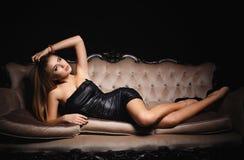 一件性感的黑礼服的美丽的女孩 库存图片