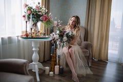 一件房子礼服的美丽的少妇在闺房,装饰用美丽的花,坐与机盖的一张白色床,启远地 免版税库存照片