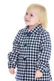 一件方格的外套的可爱的矮小的白肤金发的女孩 免版税库存照片