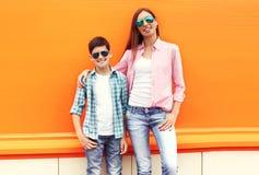 戴一件方格的衬衣和太阳镜的愉快的母亲和儿子少年 免版税库存照片