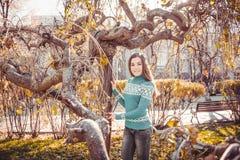 一件明亮的毛线衣的一个十几岁的女孩步行的在秋天公园 免版税库存图片