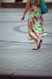 一件明亮的礼服的美丽的女孩步行沿着向下街道脚热的 库存图片