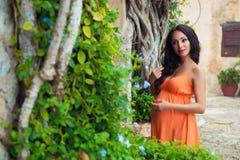 一件明亮的礼服的被晒黑的怀孕的女孩游人在热带藤本植物和村庄的老石大厦附近 免版税库存照片