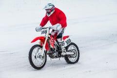 一件明亮的红色冬天夹克的摩托车竟赛者 库存照片