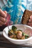 一件明亮的衬衣的人吃沙拉用土豆和芥末的 库存图片